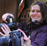 female photographer smiles while taking a picture during a photography workshop