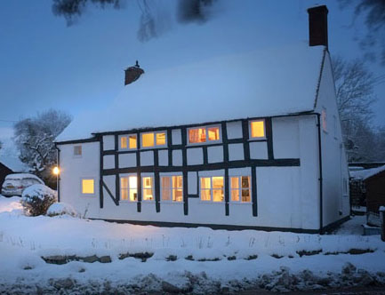 Shropshire cottage at twilight with warm glow in windows