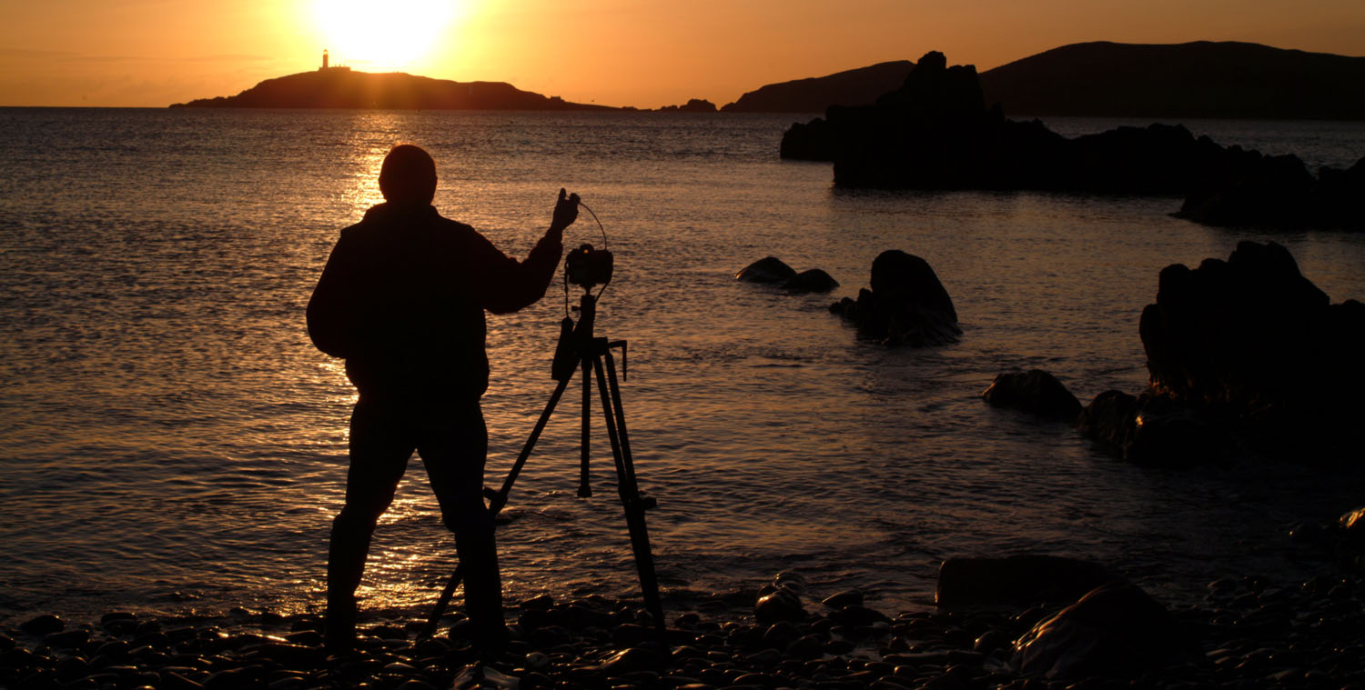 silhouette of photographer using tripod to take a picture of lighthouse at sunset