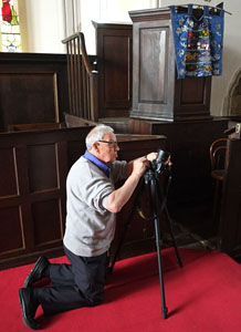 a mature male photographer kneels beside his tripod to take a picture in church