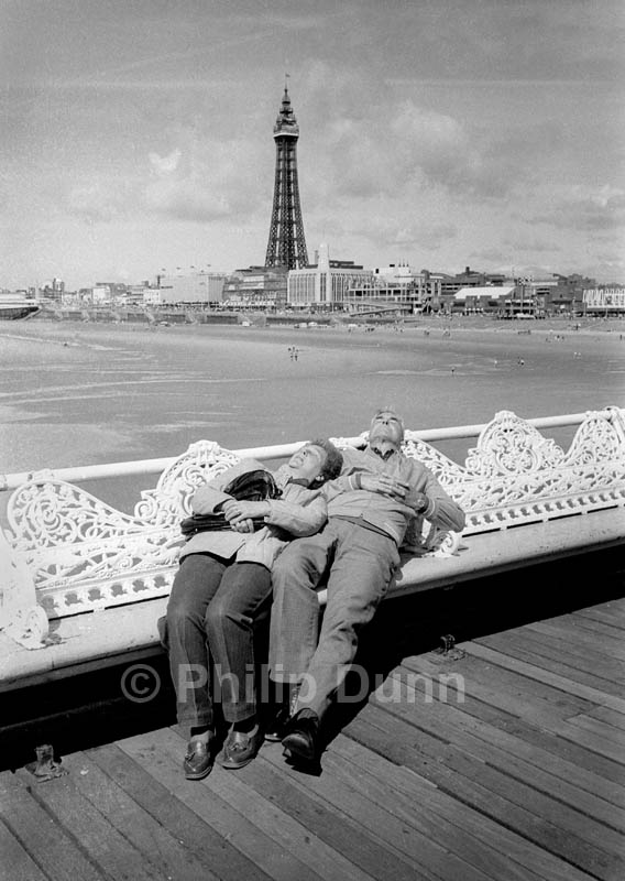 Street Photography on Blackpool pier. An elderly couple snooze with Blackpool Tower in the background