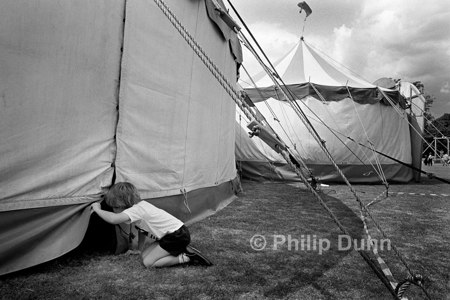 A small boy lifts the canvas of a circus tent to look inside