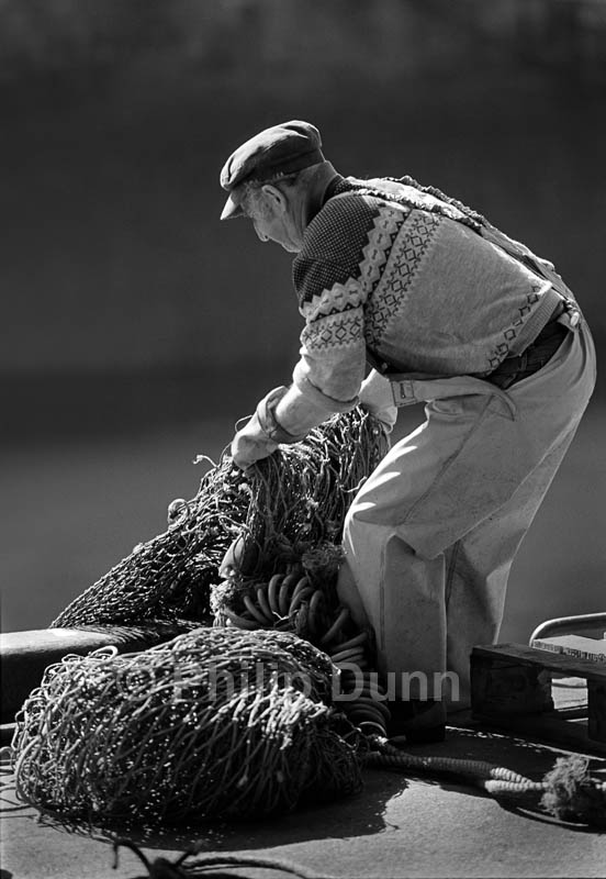Back lit photograph of fisherman with nets, Eyemouth, Britain