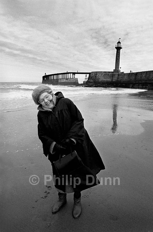 Laughing elderly lady on winter beach, Whitby, Yorkshire, England. The harbour entrance in the background