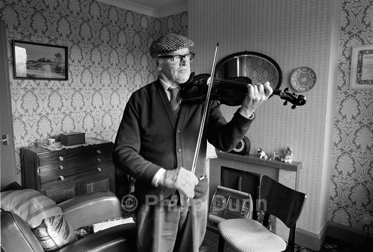 An old man wearing a cloth cap plays the violin in his front room, Stoke-on-Trent, Britain