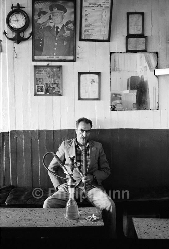 Man sits in Turkish cafe on the old Gallatti bridge, Istanbul. He smoke a hookay beneath a wall clock and photographs
