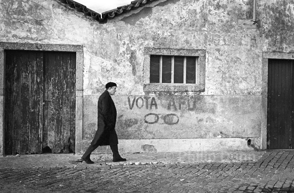 black and white image of man in black coat and beret walking past graffiti on Portuguese wal