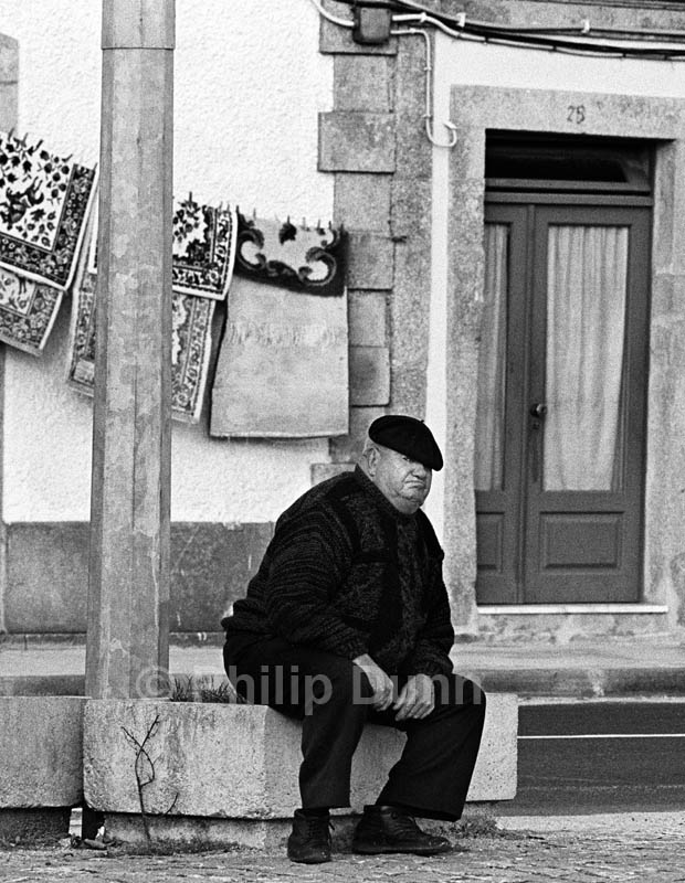 A fat, grumpy old man sits staring at the camera in an Aveiro street, Portugal