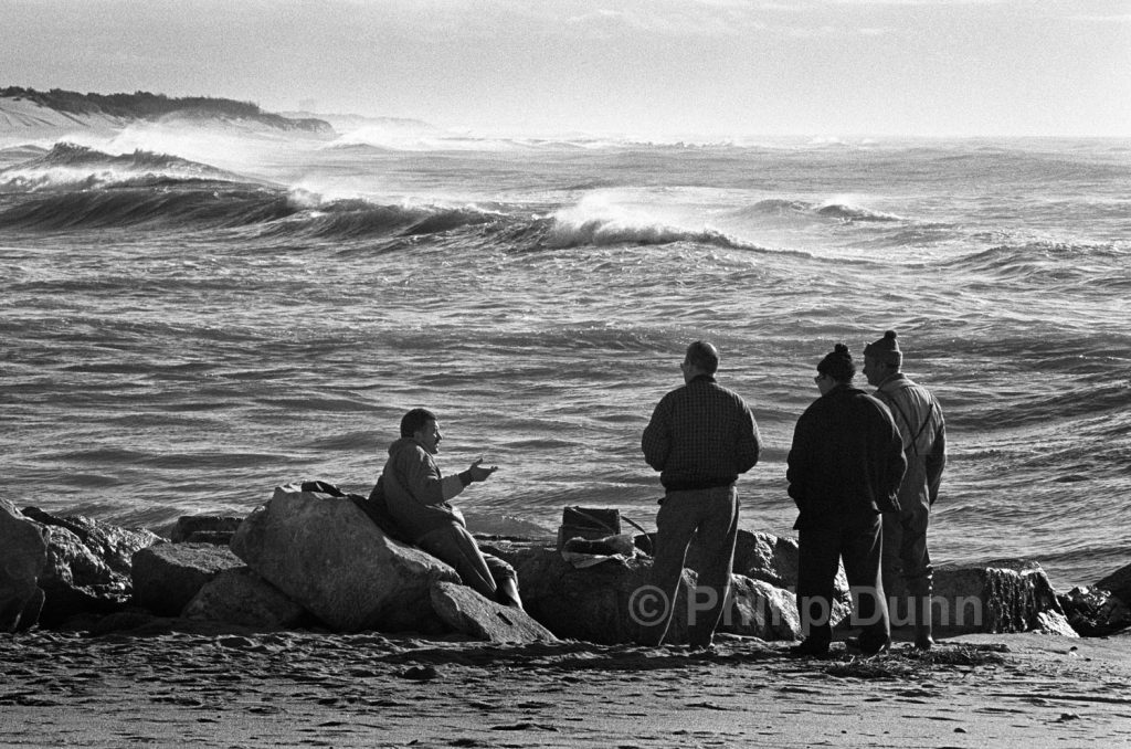 group of men talking beside huge waves off beach in Portugal