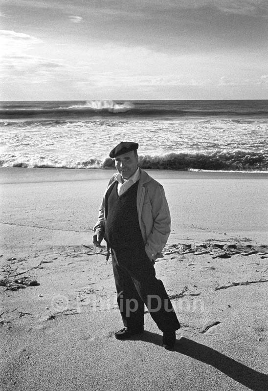 Portrait of local man wearing beret on beach, Algarve, Portugal. Breakers in the background are lit with back light