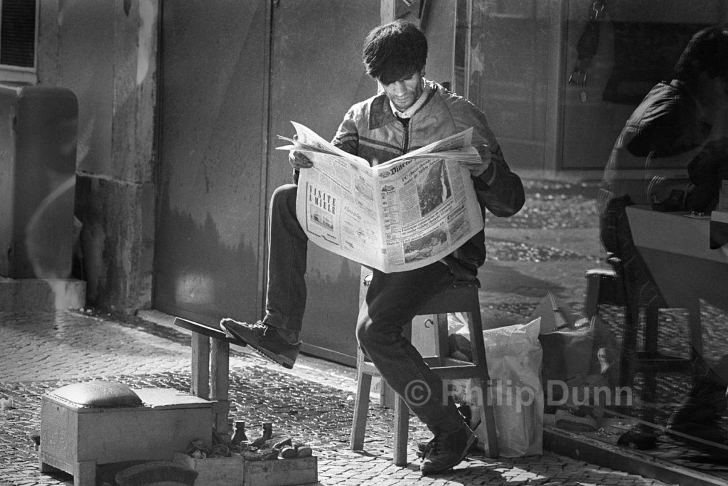 Shoe shine man reading paper, Portugal. black and white image