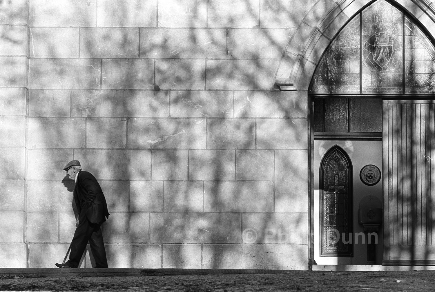 Old man leaves church along wall dappled with tree shadows, Ireland