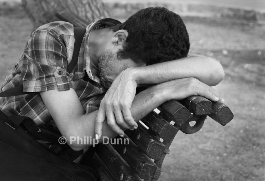 A young man falls asleep on park bench in Spain