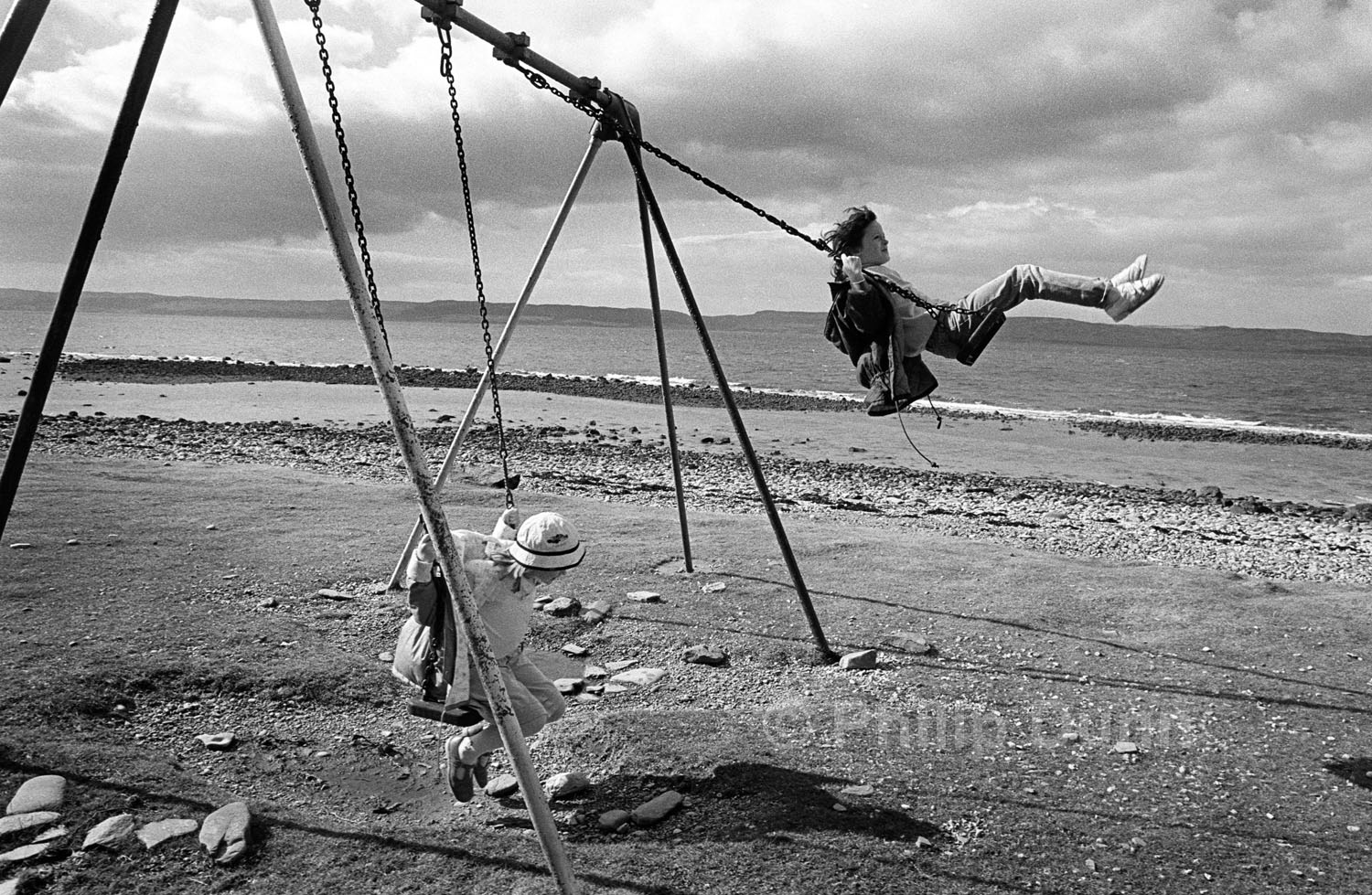 two girls on swing on Arran, Scotland. One girl swing high in the air