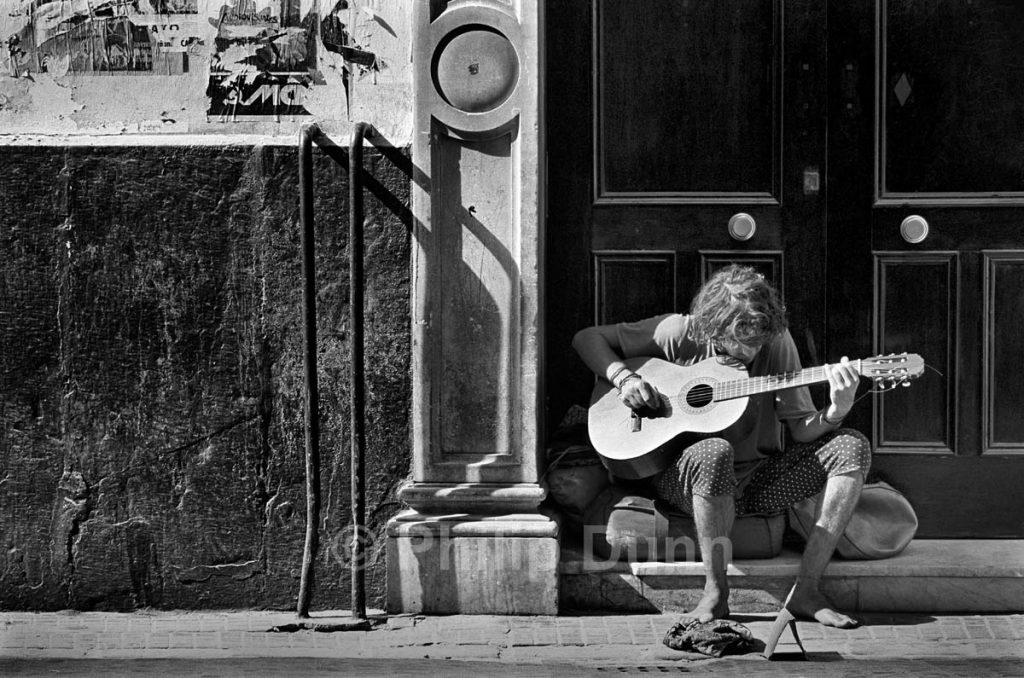 Street photograph of barefoot guitar player, Cadiz, Spain