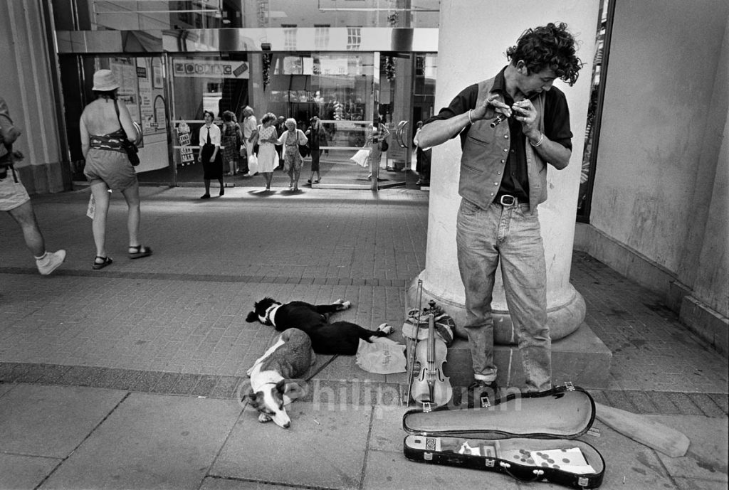 Street photography. A busker plays tin whistle outside a shopping centre while his dogs sleep