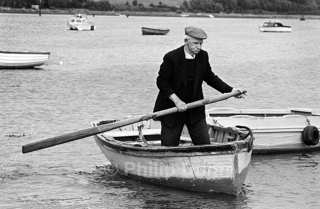 Old Irish man with one oar in a small boat