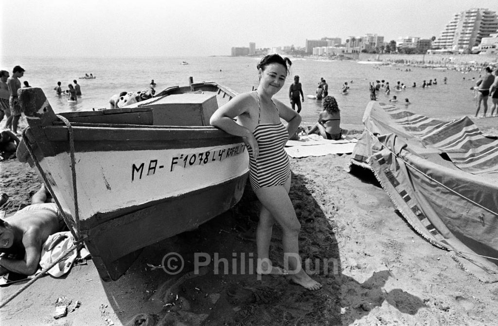 A young lady in striped swimming costume poses for photograph on Spanish beach