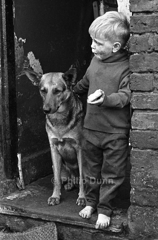 Dirty small boy stands on a slum doorstep with his dog, while eating a biscuit. Northern England 1970s