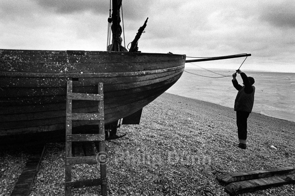 Fisherman repairs boat bowsprit line, Dungeness, Kent