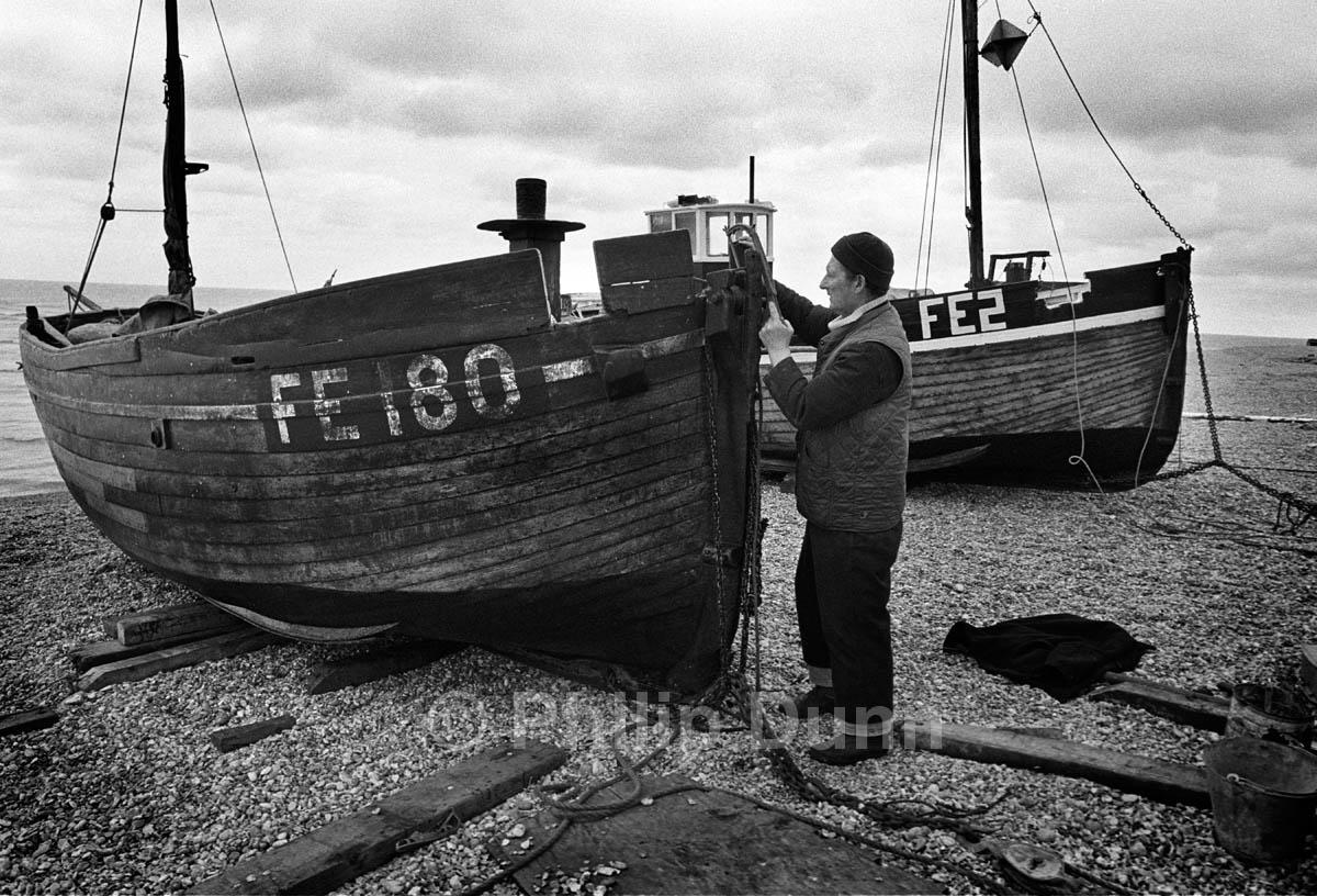 Dungeness, Kent. Fisherman prepares his wooden fishing boat on shingle beach