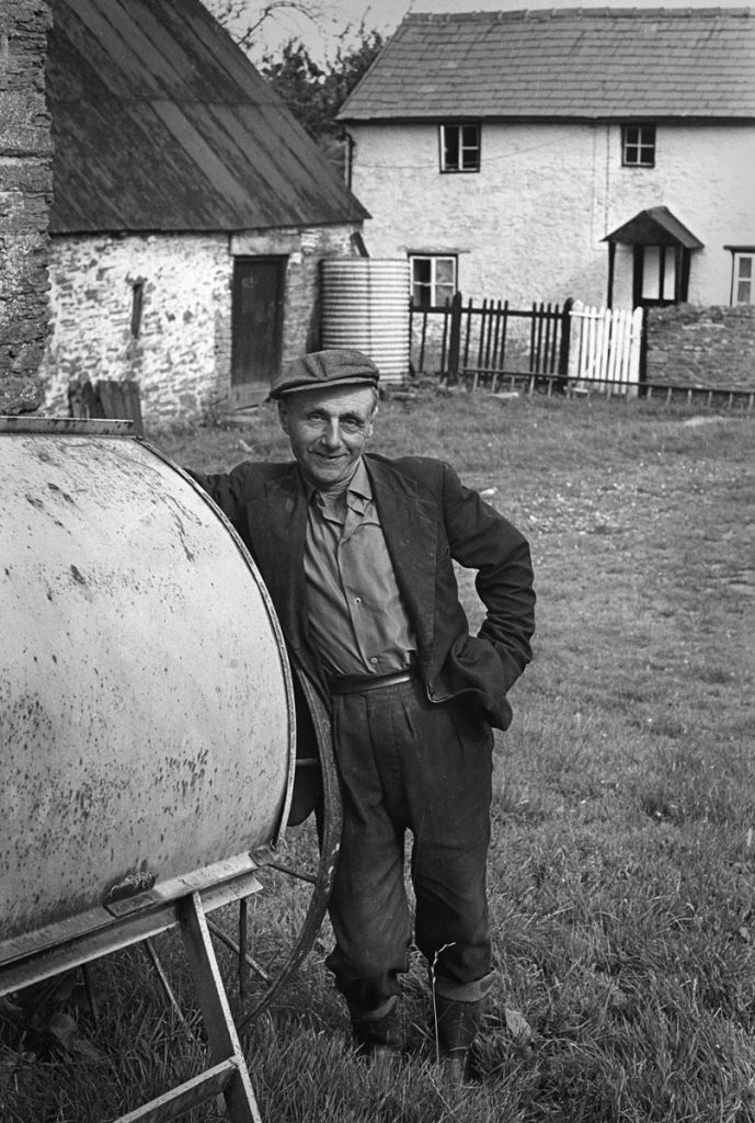 A middle aged farmer leans on a piece of machinery in his farmyard. The farmhouse is behind him