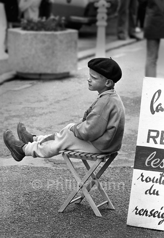 Small boy swings his legs while sat waiting outside French restaurant