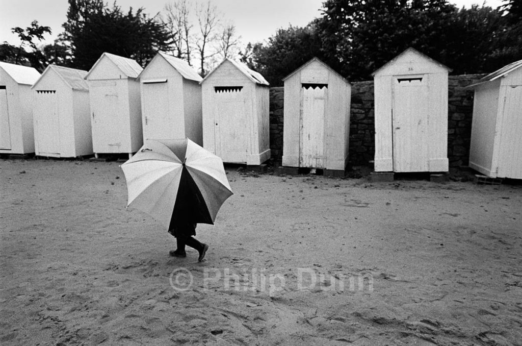 Child with large umbrella walks along beach, Bathing huts behind