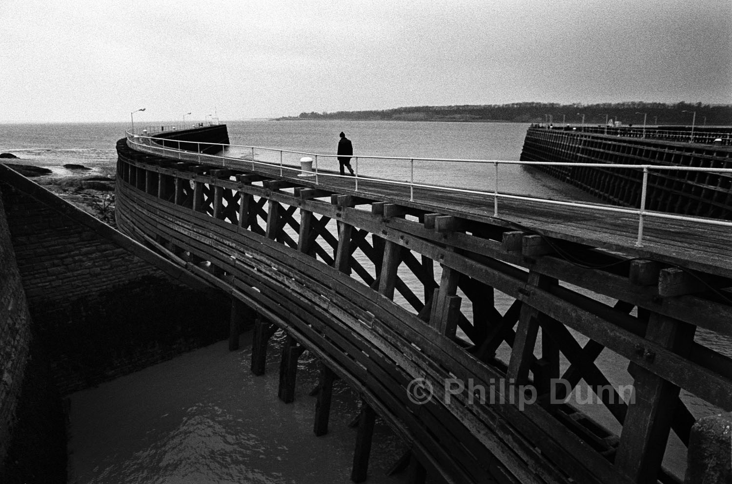 Man walks along the wooden pier in Sharpness monochrome image