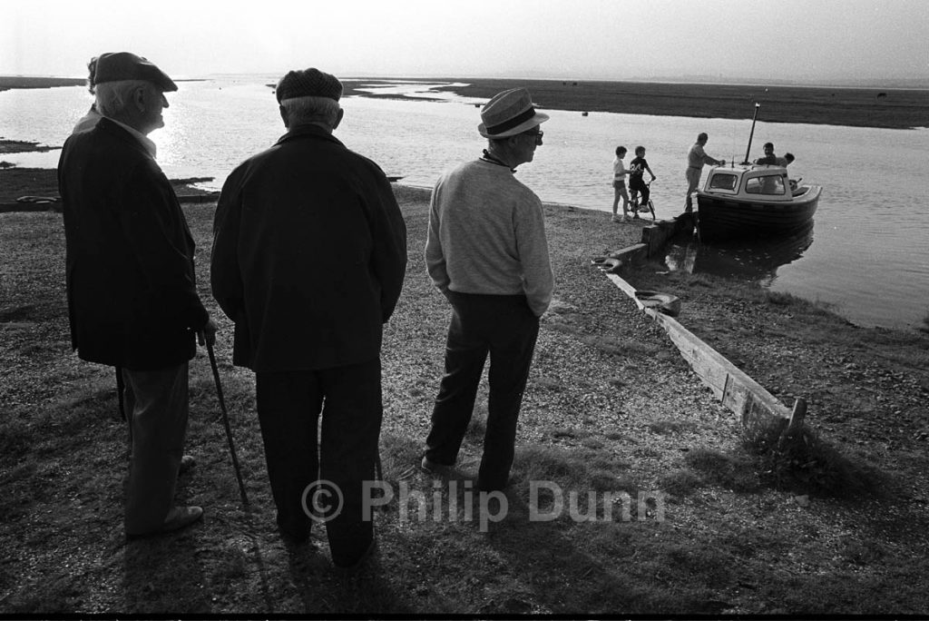 early evening an three old men watch a family launch a small boat into the tide on the Gower Peninsular, South Wals