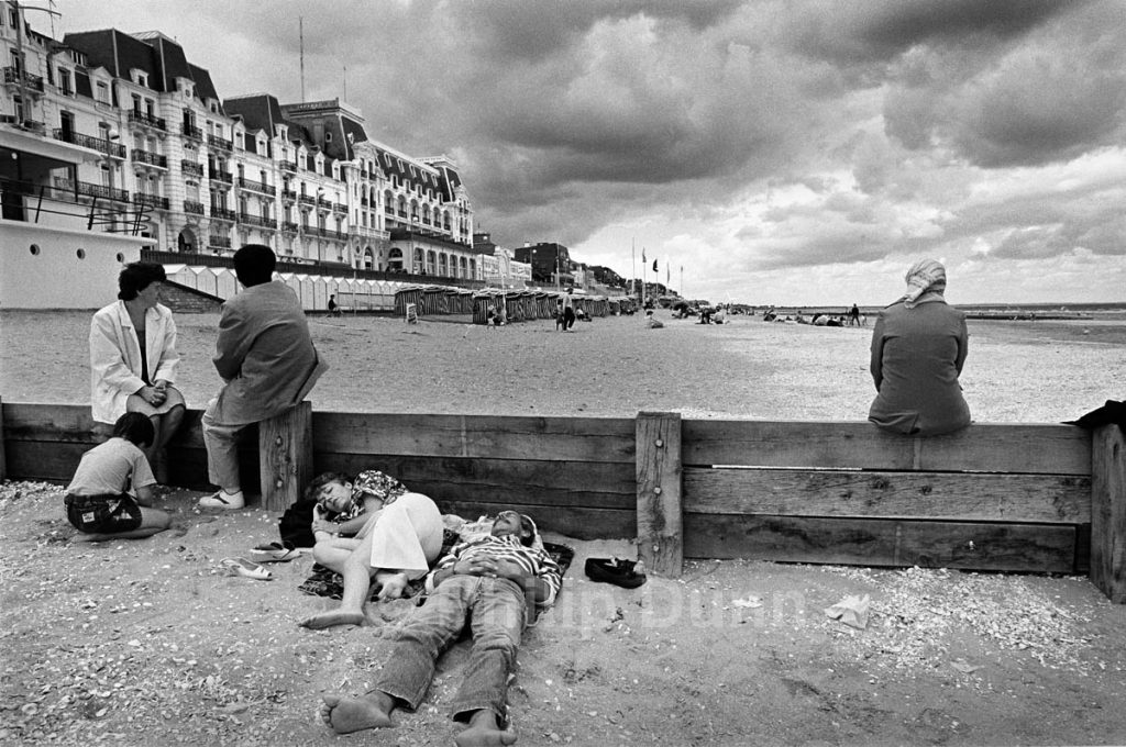 Street photograph. Family group on beach in Normandy