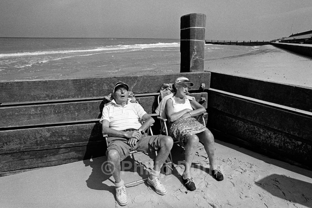 Elderly couple snooze on a Norfolk beach in shelter of a breakwater