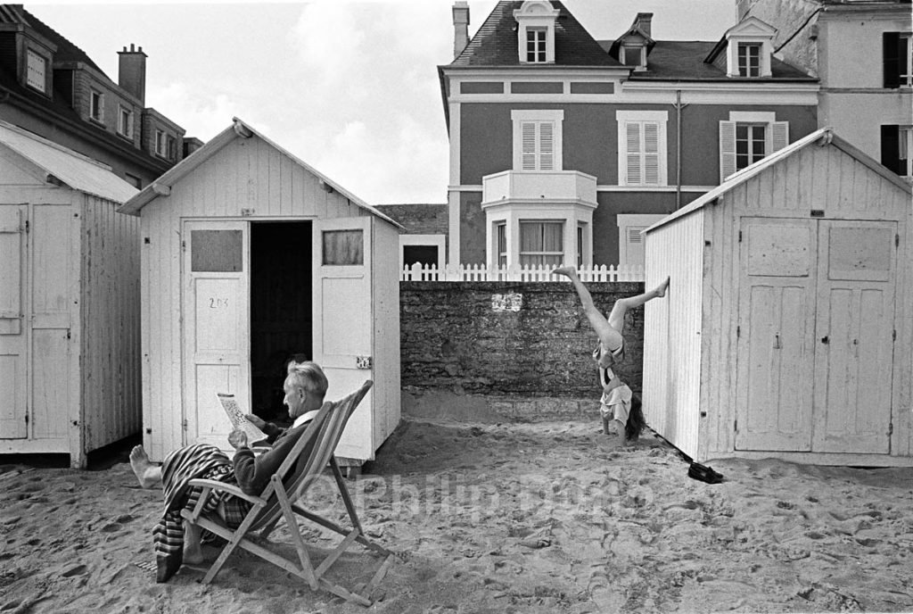 a Pensioners sits on beach unaware that a young girl is doing a handstand behind him