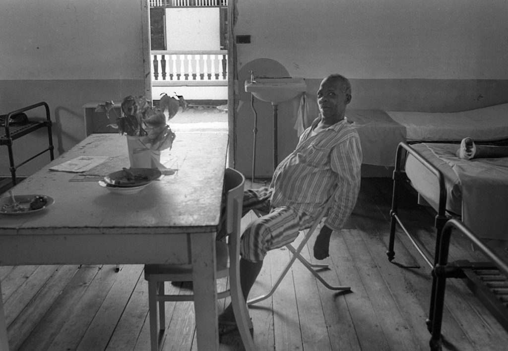 A patient recovering from an operation in a hospital in St Lucia, West Indies. He sits in his pyjamas at a table on which is a bunch of flowers