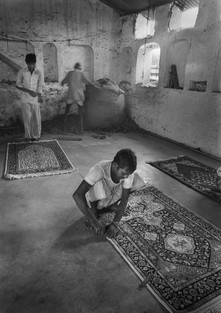 Indian carpet factory - carpet maker edges a carpet