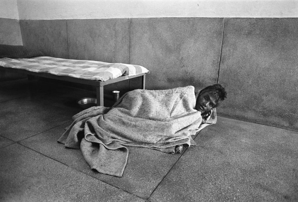 India mental health patient lies in blanket on the stone floor beside his bed. He raises his head and looks at the camera