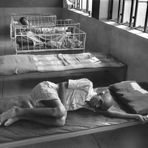 black and white photograph two male patients in an Indian mental health hospital. One lies on a naked bed, the other in a cot. Both look at the camera