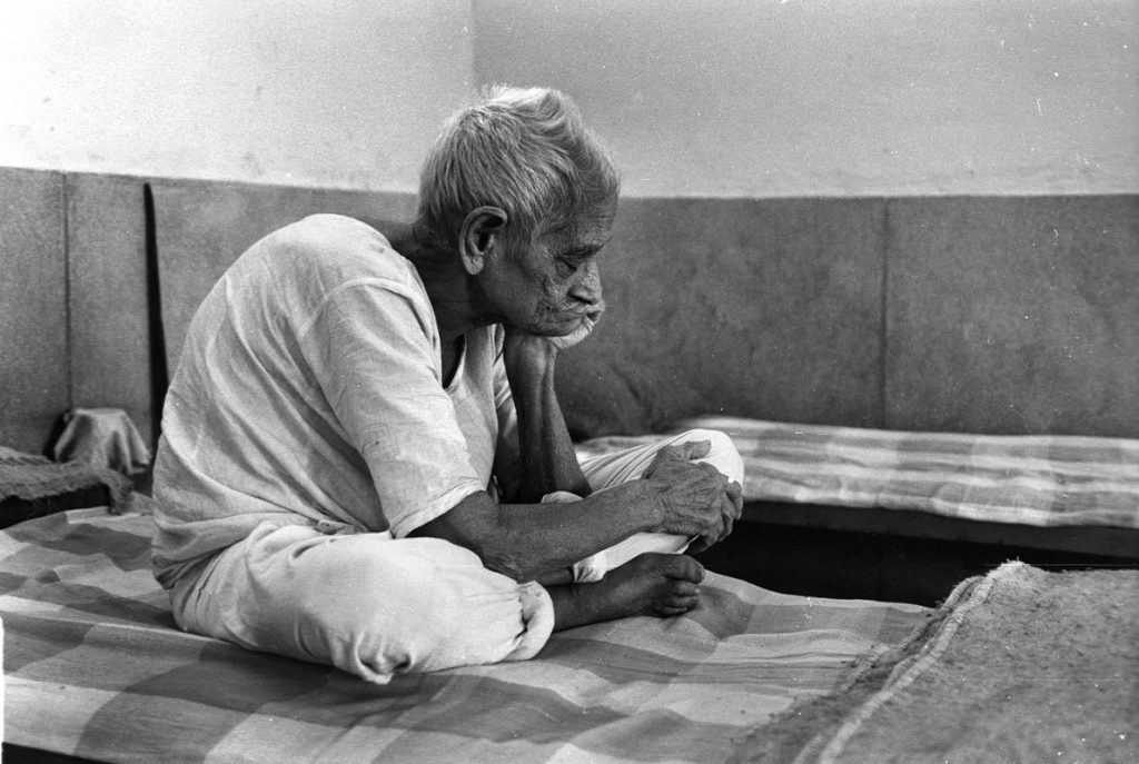 a male patient squats and doses on his bed in an India mental hospital