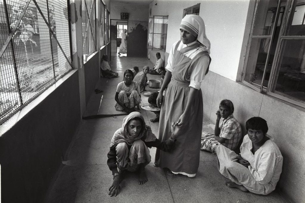 Indian mental hospital - nurse stands holding the hand of a squatting patient. Other patients, men and women watch and look at the camera