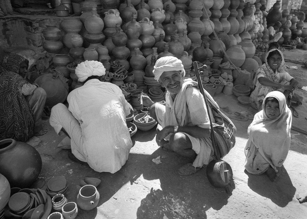A smiling man in turban knees at a stall of cooking pots in an Indian market. He carries a musical instrument and children kneel beside him