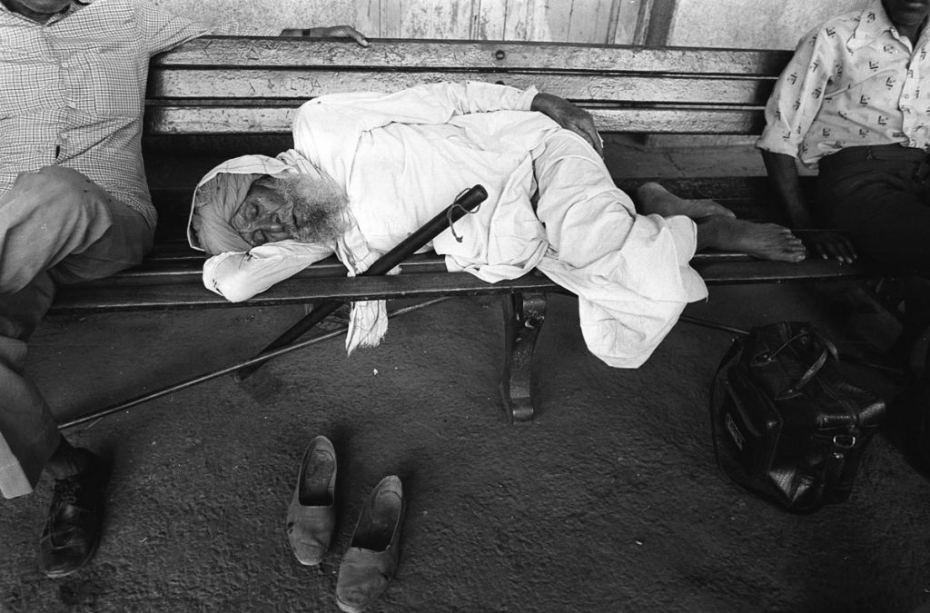 An old bearded man sleeps on a bench on an Indian Railway station. He has removed his shoes, but there is a large club beside him