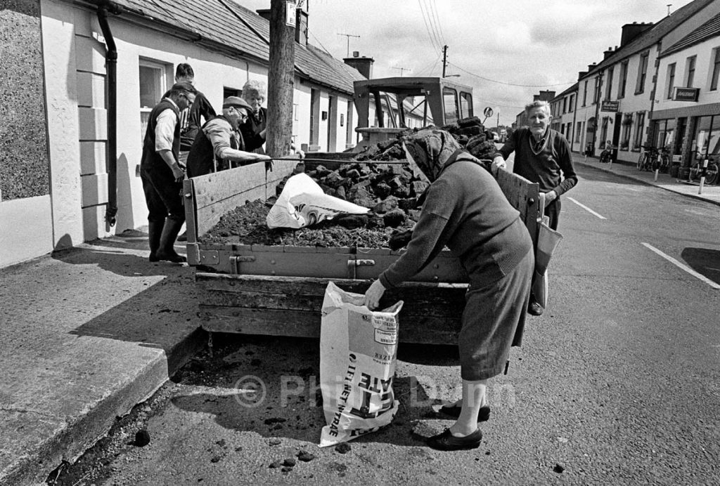 Villagers fill their bags on the street after peat delivery, Ireland