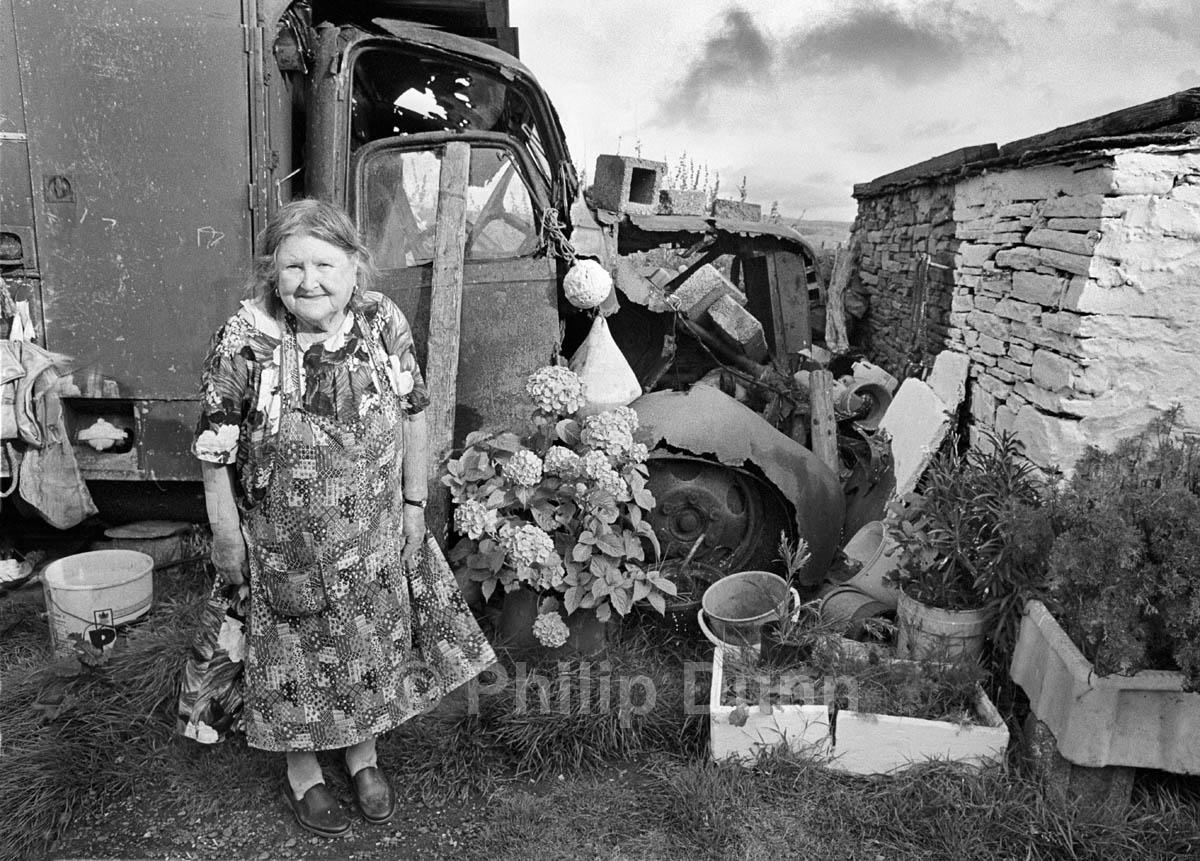 Portrait of little old Irish lady in garden full of junk