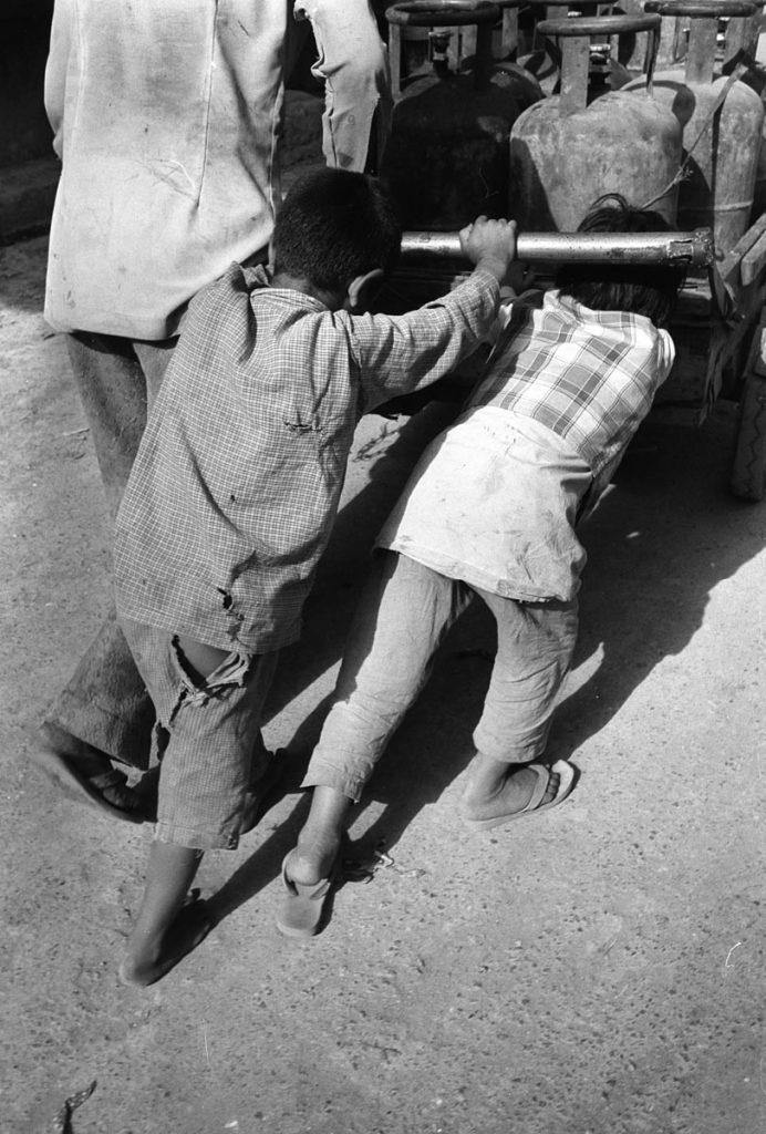 two small Kasmiri children push a heavy wheeled cart