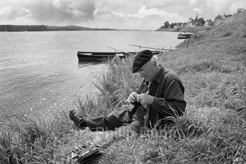 fisherman sits quietly on banks of Loire, France