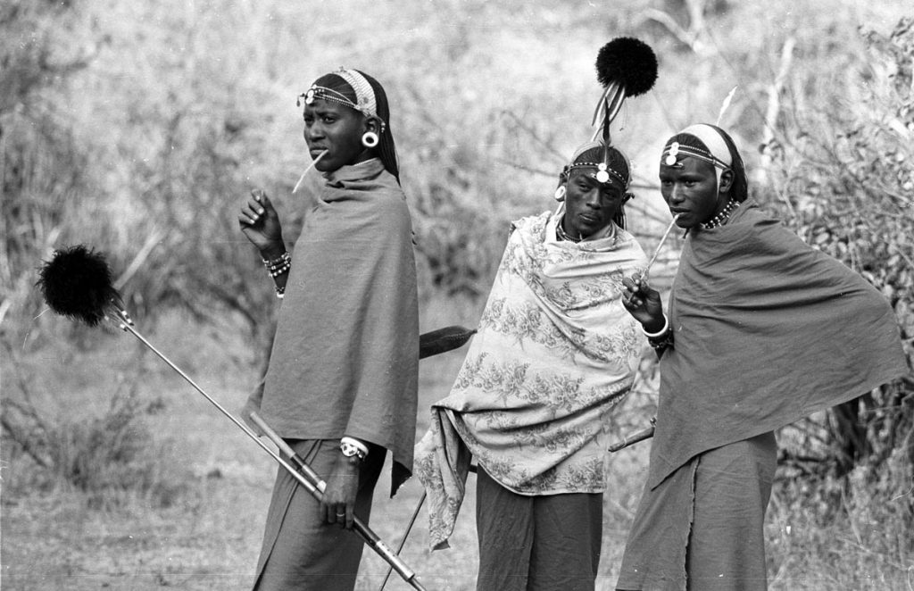 Three Masai warriors with their spears covered in su-su