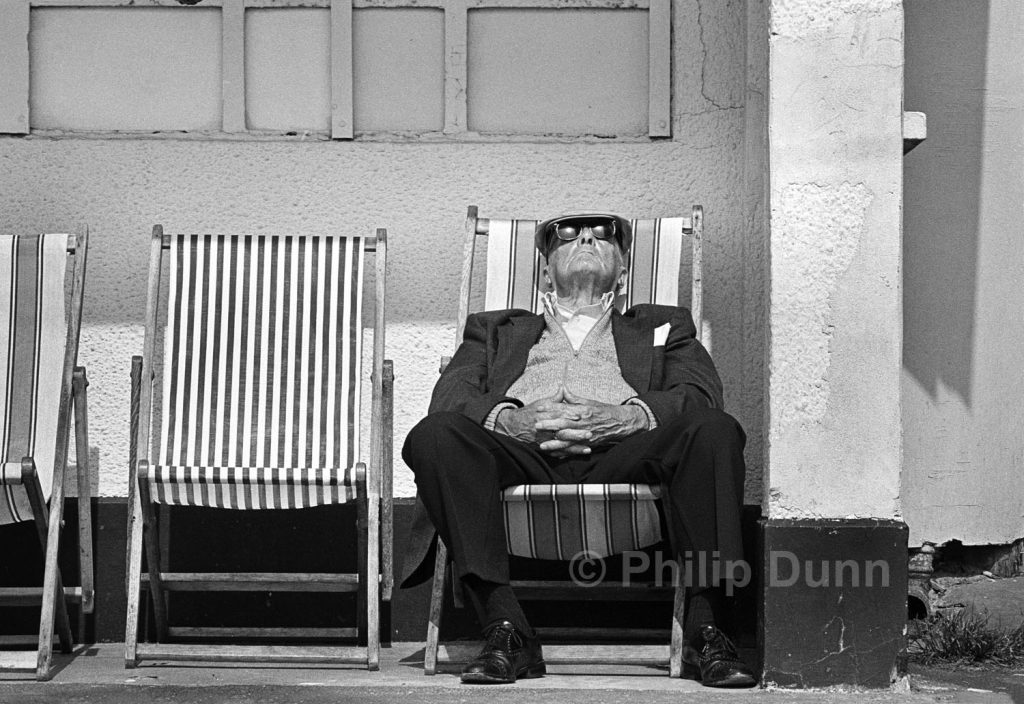Old man wearing dark glasses and cloth cap, sleeps in deck chair