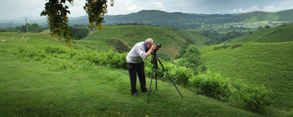 photographer with his camera on a tripod while photographing landscape in the Shropshire Hills during a photography course with Philip Dunn