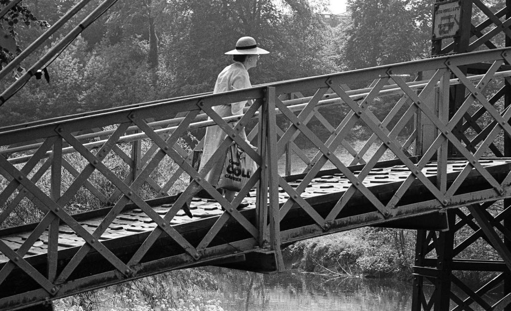 A lady in large summer hat walks across Porthill Bridge Shrewsbury - vintage image by Philip Dunn for rthe Sunday Times