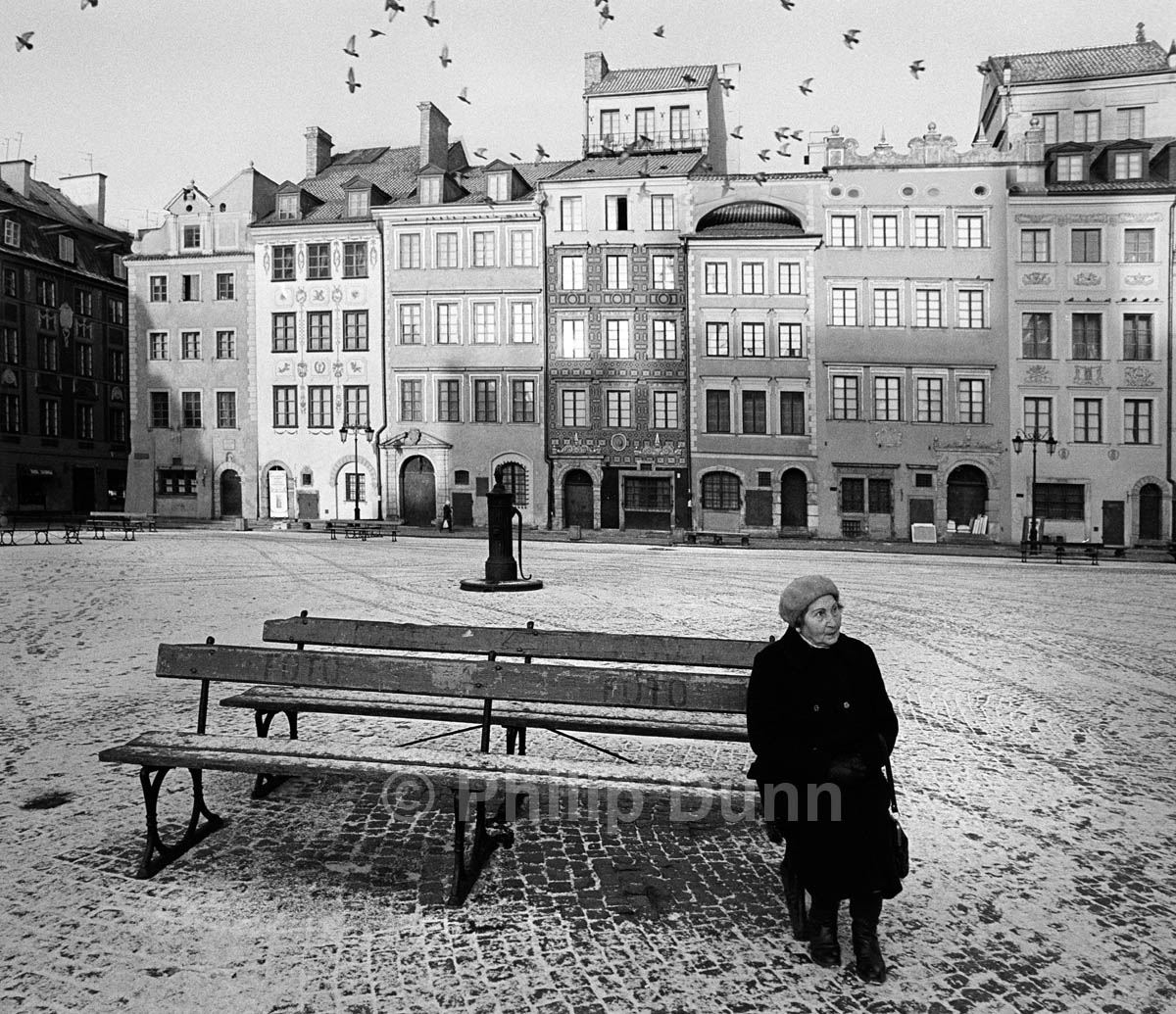 An old woman in hat sits on a bench in the snow Starigrad Square, Poland in Winter